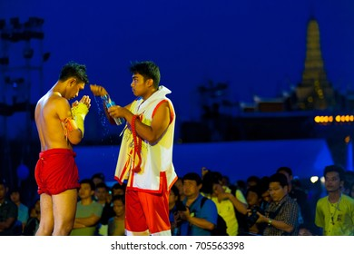 Bangkok, Thailand - April 10, 2007: Trainer pouring water over kickboxer during pre-fight ceremony at a free outdoor exhibition muay thai kickboxing match outside the Grand Palace