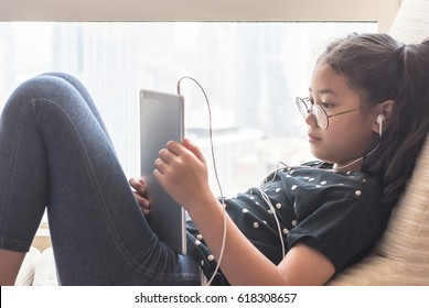 BANGKOK, THAILAND: April 10, 2017:  School kid digital technology lifestyle using wireless internet for distance learning application and reading e-book app on mobile ipad smart device computer tablet