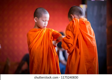BANGKOK, THAILAND – APRIL 10: Two little novices helped to clothe the cloak for monks on April 10, 2017 in Bangkok, Thailand.
