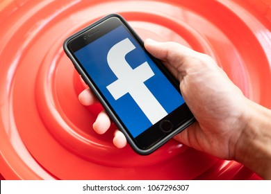 Bangkok, Thailand - April 11, 2018 : Apple iPhone 7 held in one hand showing its screen with Facebook logo.