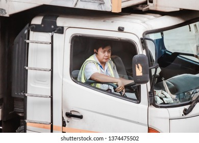 Bangkok, Thailand - April 11, 2019: Portrait of asian ground crew driving a support truck to an arriving aircraft at Suvarnabhumi airport (VTBS)