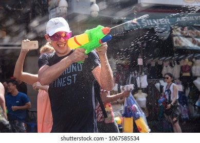 Bangkok, Thailand - April 12, 2018 : Tourist happiness fighting with water gun on the first day of water festival in Khao San Road, Let's play with soaked together in Songkran Festival Bangkok