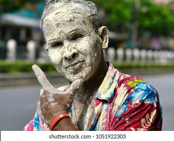 BANGKOK, THAILAND - APRIL 13, 2013: Thai man, his face covered in white paste, shows his personal version of the V sign with his left hand and poses for the camera during Songkran, on April 13, 2013.