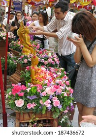 Bangkok, Thailand � April 13, 2014: People pour water over Buddha image during Songkran Days in Bangkok, Thailand. Locals and tourists throw water at each other as a part of the celebration.