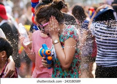 BANGKOK, THAILAND - APRIL 13, 2014: a girl playing water in Songkran festival on April 13, 2014 at Siam-Center in Bangkok