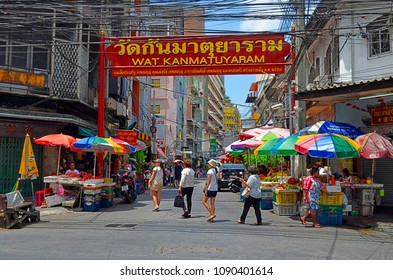 Bangkok, Thailand, April 13, 2017 - Intersection of Mangkon Road and Yaowarat Road in Chinatown, with a big red information sign for Wat Kanmatuyaram above Thai people crossing the street.
