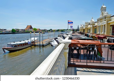 Bangkok, Thailand - April 13, 2017: The Yodpiman Riverwalk along the Chao Phraya River with the Yodpiman Pier and the Wat Arun far away in the background.