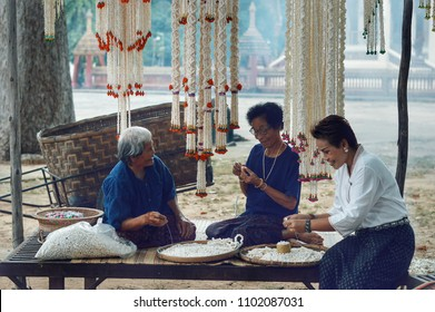 Bangkok, Thailand, April 13, 2018 : 3 old ladies make a Thai jasmine garlands for Songkran festival in Thailand.The traditional customs of Thai people.Songkran is the Thai New Year's national holiday.