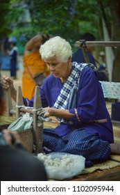 Bangkok, Thailand, April 13, 2018 : Old woman make household weaving traditional thai silk cloth for Songkran festival Thailand.The traditional customs Thai handicraft.Songkran is the Thai New Year