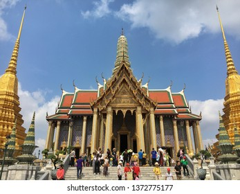 Bangkok, Thailand - April 13, 2019 : Crowd of tourists visiting at Wat Phra Kaew (the Temple of the Emerald Buddha) located inside The Grand Palace with blue sky.