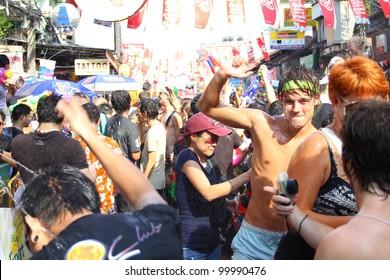 "BANGKOK, THAILAND - APRIL 13: Unidentified Thai and International people enjoy in ""Bangkok Songkran Festival 2012(Thailand new year)"" at Khao san Road on April 13,2012 in Bangkok, Thailand"