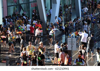 BANGKOK, THAILAND - APRIL 14,2017: Thai people and foreign travelers enjoy the Songkran Festival in Bangkok splashing water from the water guns in front of Central world department store