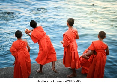 Bangkok, Thailand April 15, 2017 - The novices are feeding fish along at port waterfront of the temple