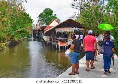 Bangkok, Thailand, April 16, 2017 - Bangkokian families walking along a klong to the entrance of Bang Nam Phueng floating market, located at Bang Kachao.