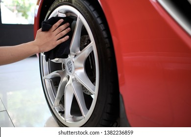 BANGKOK, THAILAND - APRIL 19, 2019: Man's hand cleaning wheel and drying Porsche Cayman with microfiber cloth. Hand wipe down inside shiny rims surface of sportscar. Car detailing and car wash concept