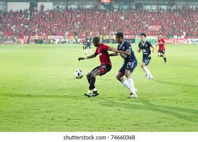 BANGKOK THAILAND - APRIL 2 :K.Christian (red) in action at Thai Premier League (TPL) between Muang Thong utd (Red) vs Buriram Fc (Blue) on April 2, 2011 at Yamaha Stadium Bangkok, Thailand