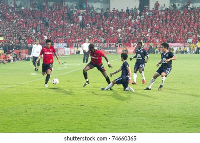 BANGKOK THAILAND - APRIL 2 Unidentified players in action during at Thai  Premier League (TPL) between Muang Thong utd (Red) vs Buriram Fc (Blue) on April 2, 2011 at Yamaha Stadium Bangkok, Thailand