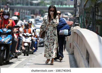 Bangkok, Thailand - April 20, 2018 A woman cover her mouth for protection against the air pollution as she walks on a street in Bangkok, Thailand.