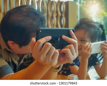Bangkok/ Thailand - April 2018: A little girl enjoys playing an edutainment app brought to her by her father on birthday.
