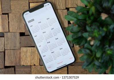 BANGKOK, THAILAND - APRIL, 2019: Woman using IPhone X with Calendar application set on screen