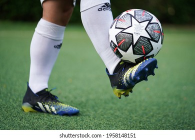 """Bangkok, Thailand - April 2021: A football player who is wear Adidas """"Predator Freak.1"""", most famous control performance stud is training football on local turf pitch. Selective focus."""