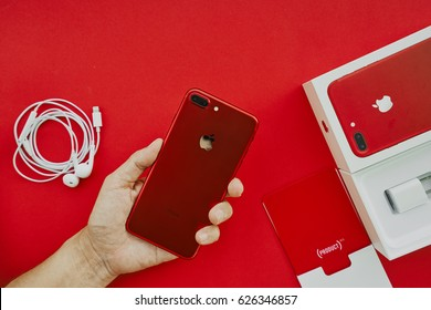 BANGKOK, THAILAND - April 22, 2017: Top view of hand holding New iPhone 7 Plus back side with accessories and package box, Special Edition of Apple Product Red