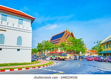 BANGKOK, THAILAND - APRIL 22, 2019: The speed traffic in Maha Rat Road with a view on tourist stores, cafes and roof of Wat Pho Buddhist Temple, on April 22 in Bangkok