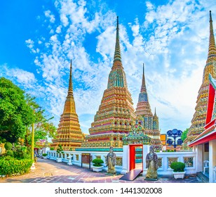BANGKOK, THAILAND - APRIL 22, 2019: The small gates with two chinese style guardians of the Phra Maha Chedi shrine's courtyard in Wat Pho complex, on April 22 in Bangkok