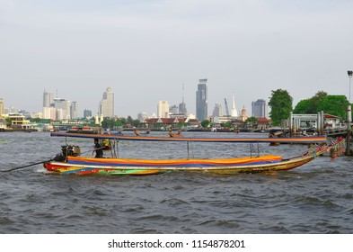 Bangkok, Thailand - April 23, 2015:  Taxi boat on the Chao Phraya River with skyscapers in the background.