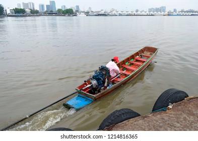 Bangkok, Thailand - April 24, 2015: Small wooden bark crossing the Chao Phraya River from Bang Kachao to Khlong Toei.