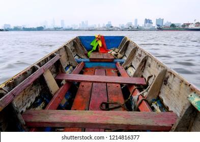 Bangkok, Thailand - April 24, 2015: Aboard a small wooden bark crossing the Chao Phraya River from Bang Kachao to Khlong Toei.