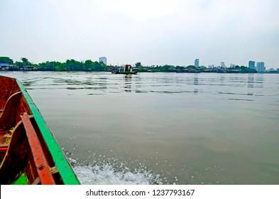 Bangkok, Thailand - April 24, 2015: Heading to Bang Kachao from Klong Toei aboard a small wooden bark under an overcast sky.