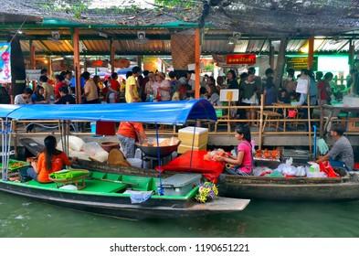 Bangkok, Thailand - April 25, 2015: Bangkokian families eating take away food bought beside the boats preparing food at Khlong Lat Mayom floating market.