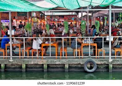 Bangkok, Thailand - April 25, 2015: Bangkokian families eating take away food bought at the stalls of Khlong Lat Mayom floating market, a nice weekend getaway.