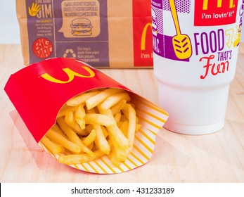 BANGKOK, THAILAND - APRIL 25, 2016: McDonald's meal on wooden background, includes coke cup, French Fries, on logo painted package.