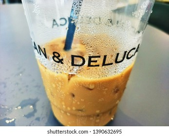 Bangkok, Thailand - April 25, 2019 : Close up Coffee Cup of Dean and Deluca On Wooden Table in Coffee shop  at Building Ploenchit Area Bangkok, Window frame of Dean and Deluca Cafe at Park Venture off