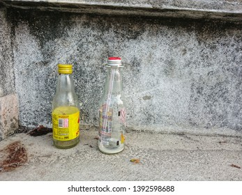 BANGKOK / THAILAND - APRIL 26, 2019 : The glass bottle after drink on the walkway roadside. The people throwing trash carelessly in anywhere not a bin. Environment negligently of human concept.