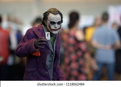 Bangkok Thailand - April 29, 2018: Figure model Joker character of Batman the dark knight from DC movies, Hand holding playing card, Realistic actor Heath Ledger, Toy exhibition show, Selective focus