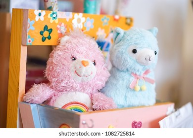 Bangkok, Thailand - April 30, 2018 : A photo of cute plush dolls or stuffed animals of a pink Care Bear and a blue alpaca are in a wooden basket. Selective focus on the rainbow on a bear's tummy.