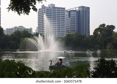 BANGKOK, THAILAND - APRIL 6, 2018: Landscape view of lakeside at Lumpini National Park with people relax on a boat in the park and city buildings lakeside.