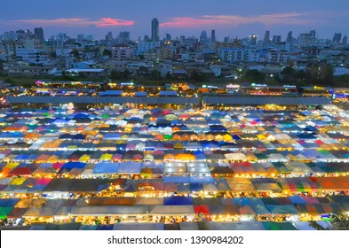 Bangkok, Thailand - April 6, 2019: High angle view of the colorful Rot Fai Night Market (meaning Train Night Market) with the multicolor tents illuminated at dusk.