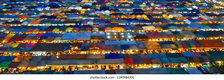 Bangkok, Thailand - April 6, 2019: Panoramic high angle view of the colorful Rot Fai Night Market (meaning Train Night Market) with the multicolor tents illuminated at dusk.
