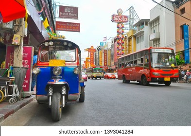 Bangkok, Thailand - April 7, 2019 : Low angle view of the bustling Yaowarat Road in Chinatown with a tuk-tuk in the foreground.