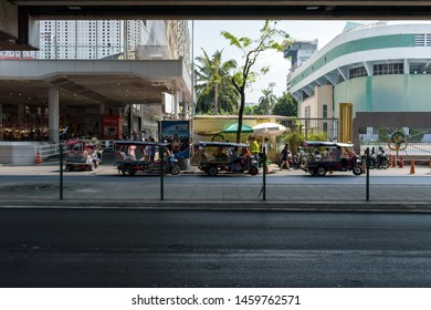 Bangkok, Thailand. April 7, 2019. Street scene right below the BTS Sky Train National Stadium station showing a row of Thai Tuk Tuk public transport lining at the side of the road.