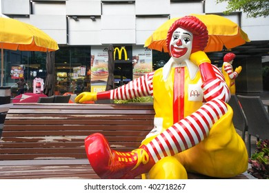 BANGKOK, THAILAND - APRIL 8, 2016 : Portrait of of Ronald-Mcdonald sitting on bench in front of McDonald's restaurant. McDonald's operates in 119 countries with 160 stores in Thailand. Selective Focus