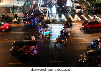 Bangkok, Thailand - April 8, 2019 : Traffic congestion at night on the streets of Bangkok at Siam Station. It is filled with cars, buses, motorcycles and motorised trishaws call tuk tuk