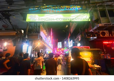 Bangkok, Thailand - April 8, 2019: Adult tourists walking in a motion blur under the information sign at the entrance of Soi Cowboy, one of the red light district areas of Bangkok.