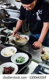 BANGKOK, THAILAND. AUG 10, 2016: Chef making Hakata style Chashu Ramen by holding ramen noodle in Shio soup with chopsticks.