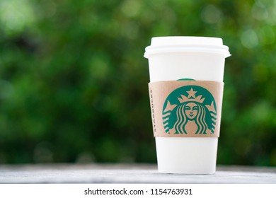 Bangkok, Thailand - Aug 13, 2018: a cup of Starbuck coffee on the wooden table outdoor