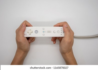 Bangkok, Thailand - Aug 19, 2018 : Wii, Hands holding the home video game controller produced by Nintendo, isolated on white background.